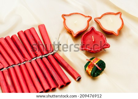 Firecrackers and Diwali lamp on silk background, Diwali festival India Asia South East Asia - stock photo