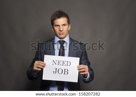 Fired businessman searching for a job isolated on gray background - stock photo