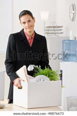 Fired businesswoman carrying box - stock photo
