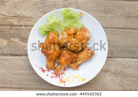 Fired chicken on wood table.focus on front piece of chicken.