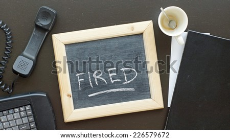 Fired written on a chalkboard at the office - stock photo