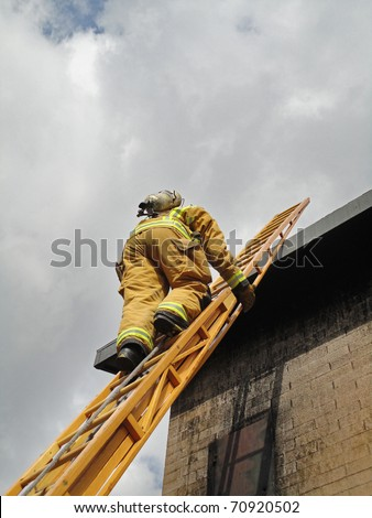 Firefighter ascends on a twenty-four wooden extension ladder. - stock photo