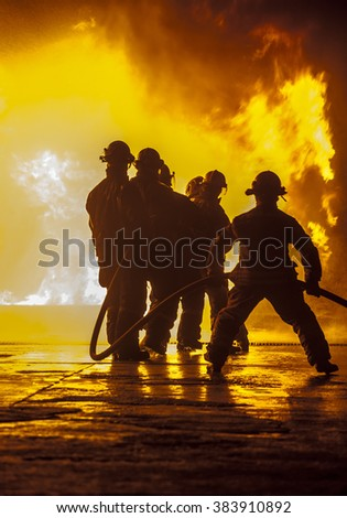Firefighter bracing during firefighting - stock photo