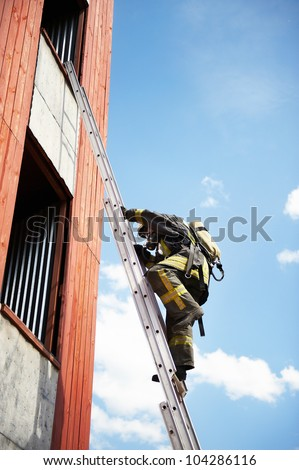 Firefighter climb on fire stairs to window - stock photo