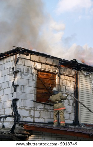 firefighter extinguishing a fire in flaming house - stock photo