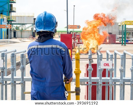 Firefighter, fire fighter,  firemen, fireman, ignite fire by discharge oil through pipeline for preparing fire during conflagration preventive extinguisher training, Safety concept. - stock photo