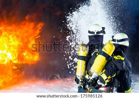 Firefighter - Firemen extinguishing a large blaze, they are standing with protective wear in front of wall of fire - stock photo