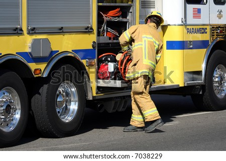 Firefighter getting equipment from his fire truck - stock photo