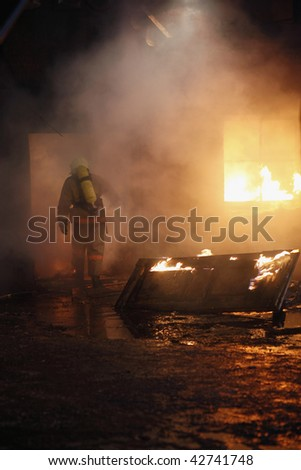 Firefighter going to rescue in a fire. - stock photo
