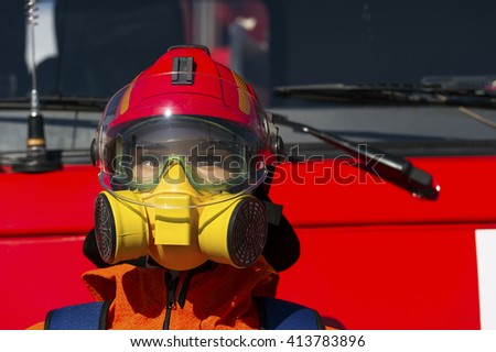 Firefighter hard hat, breathing mask or respirator with interchangeable filter cartridges and safety goggles on mannequin with red truck on background, fireman protective means, rescue service - stock photo