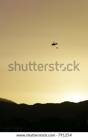 Firefighter helicopter flying over mountains to fire at sunset