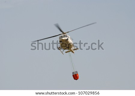 Firefighter helicopter in flight carrying an extinguihsing bucket - stock photo