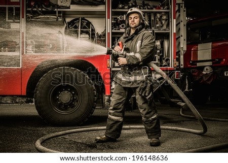 Firefighter holding water hose near truck with equipment  - stock photo