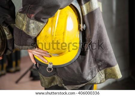 Firefighter Holding Yellow Helmet - stock photo