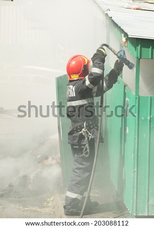 Firefighter in action - Fireman extinguishing a fire - stock photo