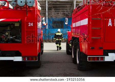 Firefighter in protective clothing about fire trucks - stock photo