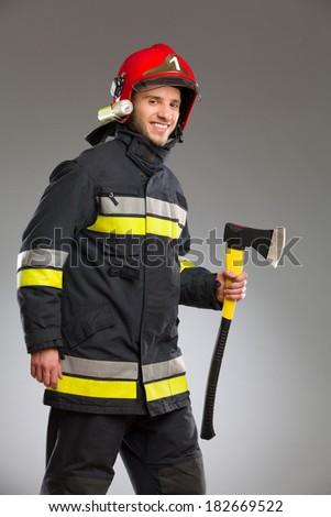 Firefighter in red helmet holding axe. Three quarter length studio shot on gray background. - stock photo