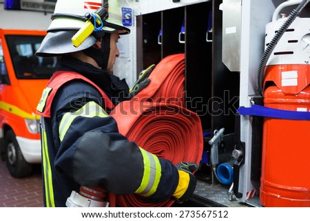 Firefighter in the fire station with hose - stock photo