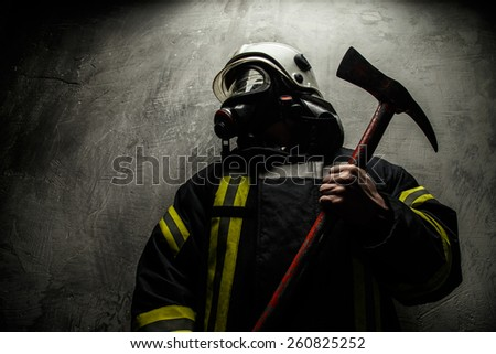 Firefighter in uniform with axe on grey background - stock photo