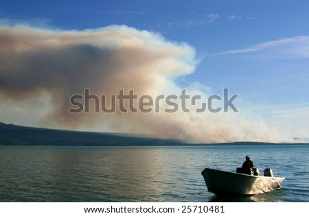 Firefighter On Boat Near Large Wildfire - stock photo