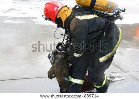 Firefighter pulling away a dummy during a drill