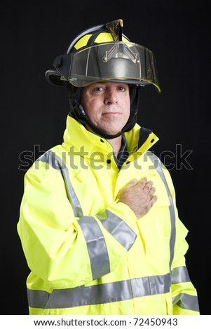 Firefighter says the Pledge of Allegiance with his hand on his heart.  Black background. - stock photo