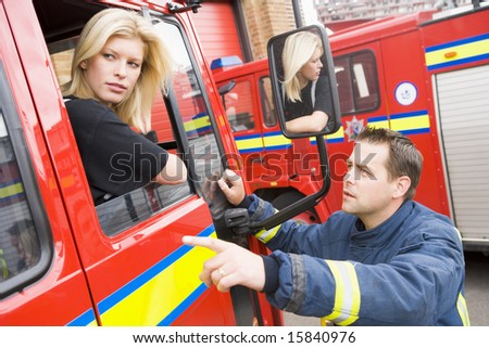 Firefighter sitting in the cab of a fire engine talking to a co-worker - stock photo