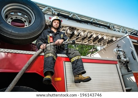 Firefighter sitting on a firefighting truck with water hose  - stock photo