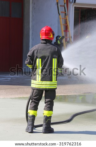 Firefighter sprays water with the spear fighting during the exercise in the fire hall