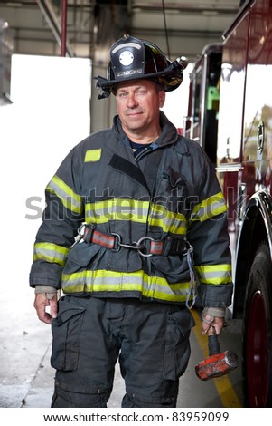 Firefighter standing in front fire truck portrait