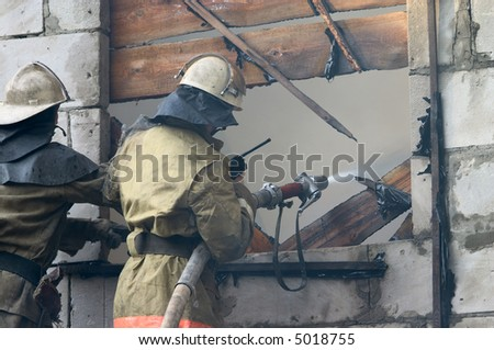 Firefighter with firehose spraying water in window of flaming house - stock photo