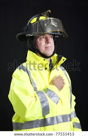 Firefighter with his hand over his heart, pledging allegiance to the flag. - stock photo