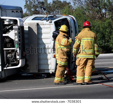 Firefighters at the scene of a turned truck - stock photo