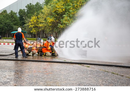Firefighters attack fire during a training exercise. - stock photo
