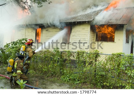 Firefighters battle house on fire - stock photo