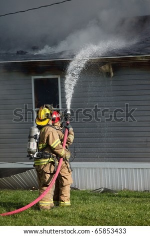 Firefighters fight a fire with a water hose that started in a residential house and someone's home. - stock photo