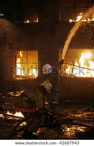 Firefighters fighting a fire - stock photo