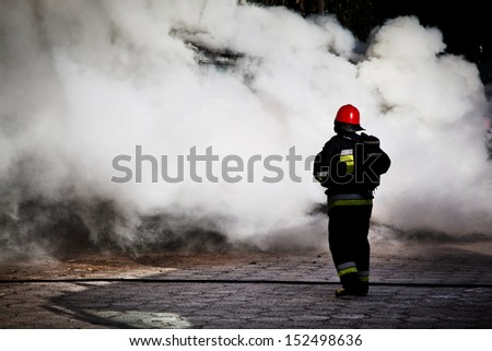 Firefighters fighting a fire of a waste place. Cloud of smoke surrounding  - stock photo