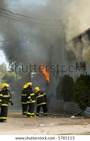 Firefighters fighting  burning building in Quebec country, Canada - stock photo