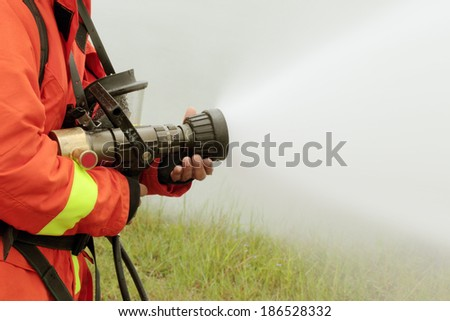 Firefighters fighting fire with pressured water during training  - stock photo