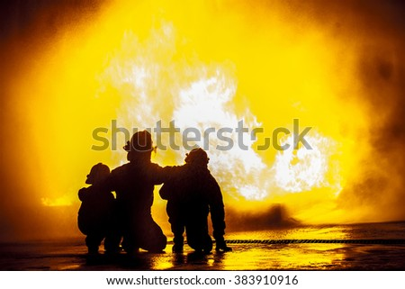 Firefighters in front of a burning tank