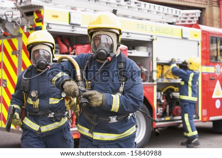 Firefighters in protective workwear - stock photo