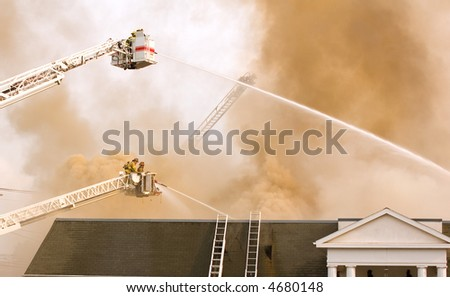 firefighters in the smoke from burning building - stock photo