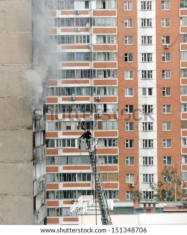 Firefighters on hose attack the fire in apartment building - stock photo
