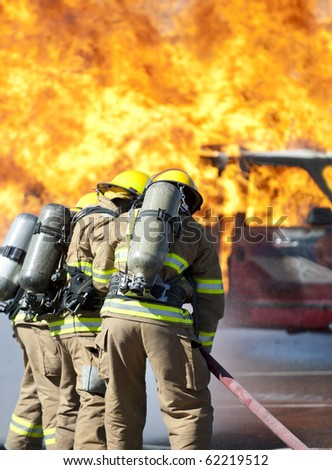 Firefighters prepare to attack a propane fire during a training exercise. - stock photo
