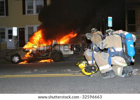 Firefighters prepare to battle car fire - stock photo