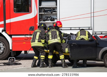 Firefighters pull in wounded by car plates after highway crash - stock photo