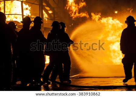 Firefighters putting out burning structure with water - stock photo