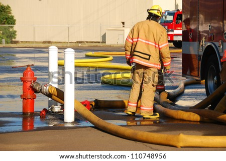 Firefighters setting up supply lines at a heavy streams fire training - stock photo