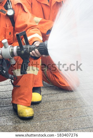 Firefighters spray water - stock photo